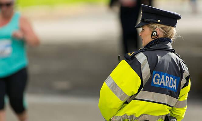 Female Garda Officer watching marathon runners