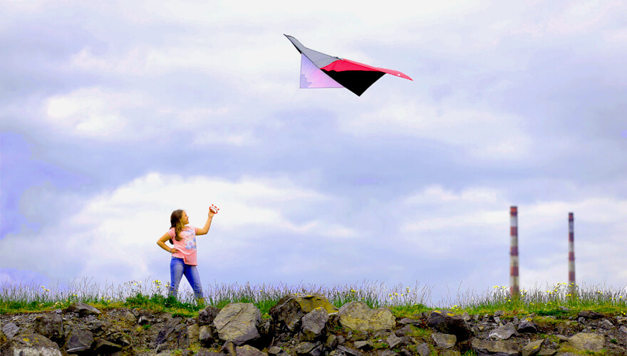 Girl flying a kite with the Poolbeg Lighthouse in the background
