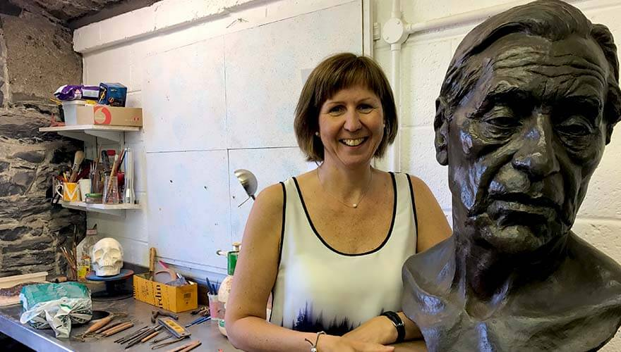 Elizabeth standing beside a completed bust